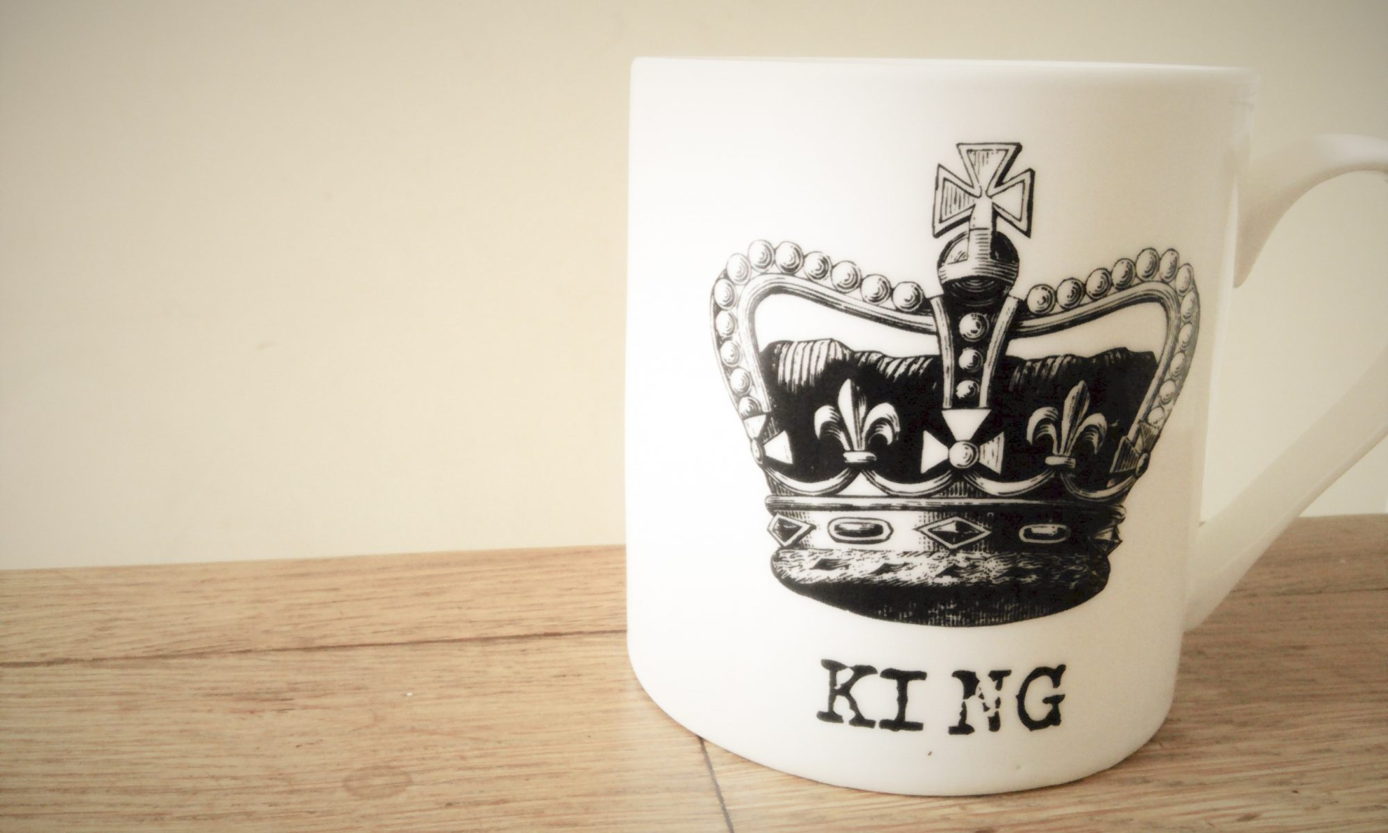 a white mug with a crown & words King